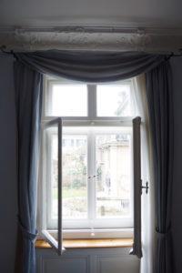Kastenfenster mit Stuck und Gardinen